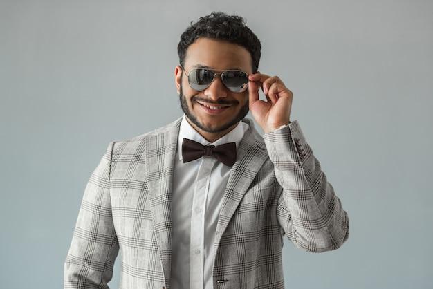 Afro amerykanin w garniturze, muszce i okularach przeciwsłonecznych