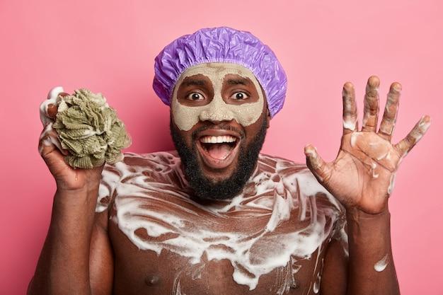 Afro amerykanin z glinianą maską, na białym tle wyraża pozytywne emocje