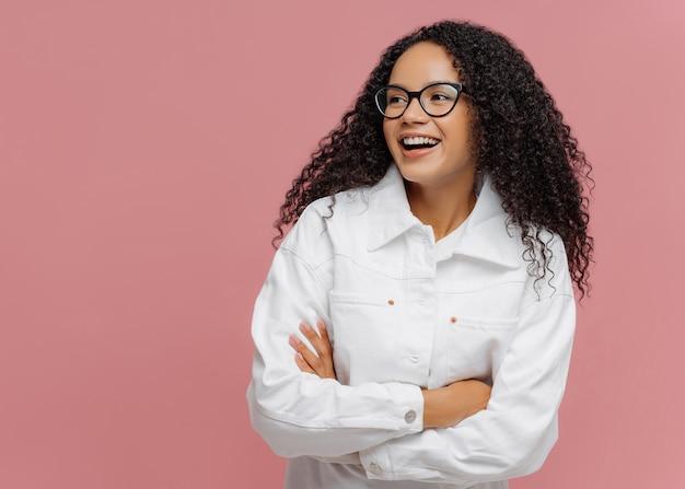 Afro amerykanka nosi białą kurtkę, trzyma złożone ręce, wygląda na bok, ma uroczy uśmiech