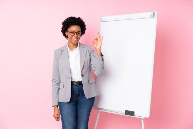 Afro amerykańska biznesowa kobieta nad menchii ścianą