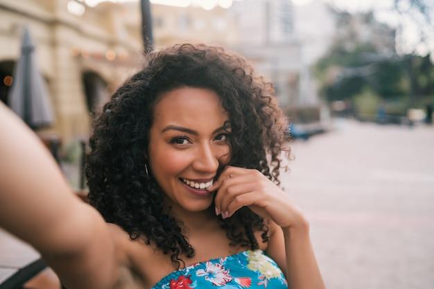 Afro amerykańska kobieta bierze selfie w mieście.