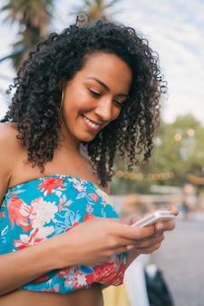 Afro amerykańska kobieta łacińskiej za pomocą telefonu komórkowego.