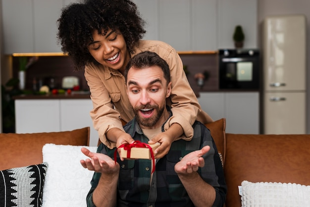 Afro-amerykańska kobieta oferuje prezent swojemu chłopakowi