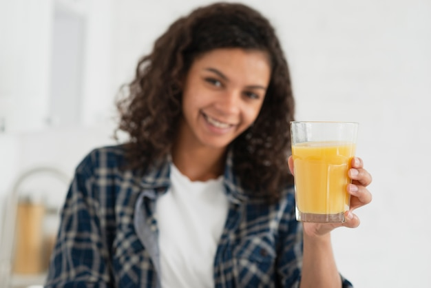 Afro amerykańska kobieta oferuje sok pomarańczowego