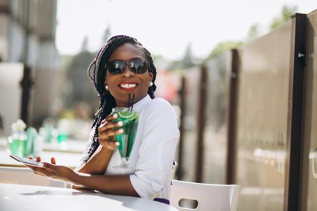 Afro amerykańska kobieta pije w kawiarni z telefonem