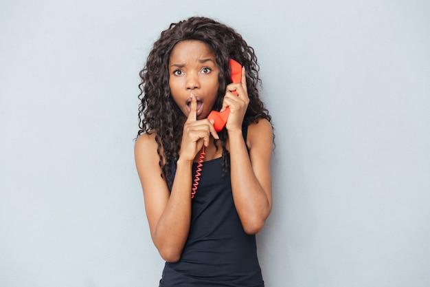 Afro amerykańska kobieta rozmawia przez retro rurkę telefoniczną i pokazuje palec nad ustami nad szarą ścianą