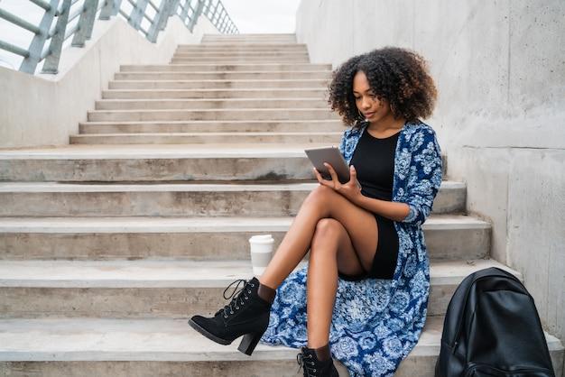 Afro amerykańska kobieta używa cyfrową pastylkę