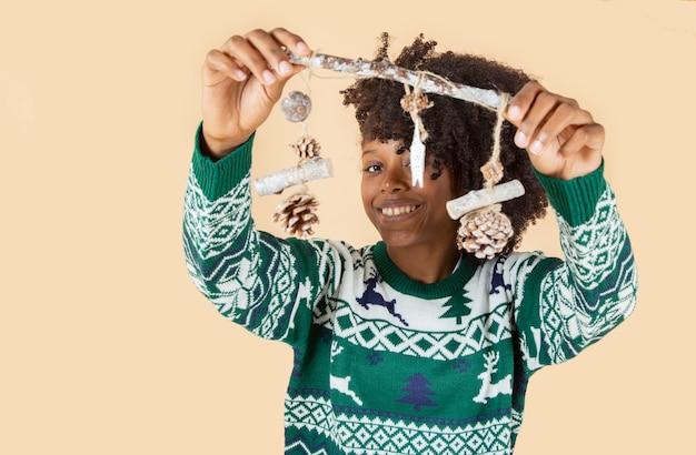 Afro amerykańska kobieta z bożonarodzeniowymi dekoracjami nowy rok beżowym tle