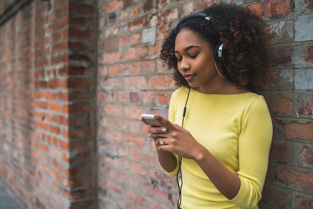 Afro-amerykańska kobieta z telefonem komórkowym i hełmofonami