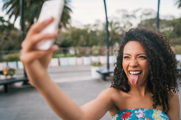 Afro amerykańska łacińska kobieta bierze selfie z telefonem.