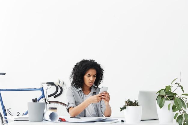 Afro amerykańska młoda bizneswoman posiadająca smartfona posiadająca specyficzny wygląd