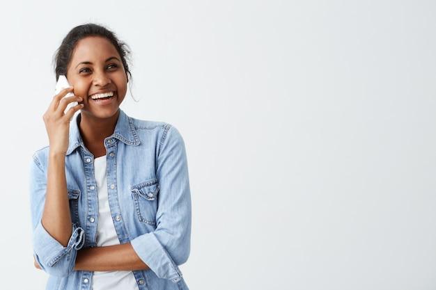 Afro-amerykańska młoda uradowana kobieta ubrana w niebieską koszulę na białej koszulce rozmawiająca przez smartfon, śmiejąca się, dzieląca się dobrymi wieściami z przyjaciółmi. ludzie i pozytywne emocje.