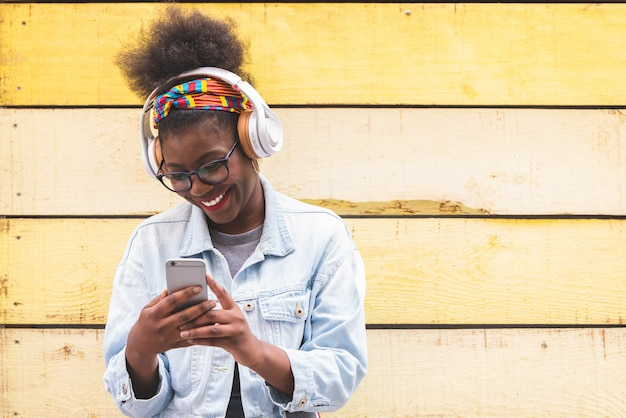 Afro amerykańska nastoletnia dziewczyna używa telefon komórkowego outdoors.