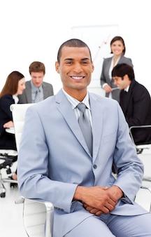 Afro-amerykański biznesmen siedział przed kolegami