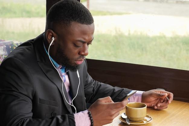 Afro amerykański biznesmen w kawiarni. murzyn słucha muzyki w słuchawkach przegląda telefon komórkowy i pije kawę siedząc w kawiarni. facet ma na sobie koszulę i marynarkę. ciesz się poranny czas.