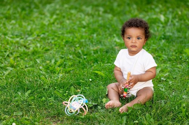 Afro-amerykański chłopczyk na zielonym trawniku w lecie gry, miejsce na tekst