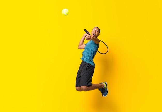 Afro amerykański gracz w tenisa mężczyzna na kolorze żółtym