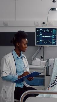 Afro amerykański lekarz piszący ekspertyzę medyczną w schowku monitorującym objawy choroby, pracujący na oddziale szpitalnym. kobieta asystująca zażywająca tabletki na chorobę podczas wizyty rekonwalescencyjnej