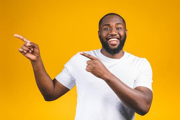 Afro amerykański mężczyzna nad odosobnioną ścianą zadziwiał i ono uśmiecha się podczas gdy przedstawiający z ręką i wskazujący palcem.