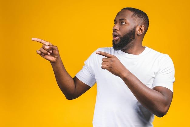 Afro amerykański mężczyzna nad odosobnioną ścianą zadziwiał podczas gdy przedstawiający z ręką i wskazujący palcem.