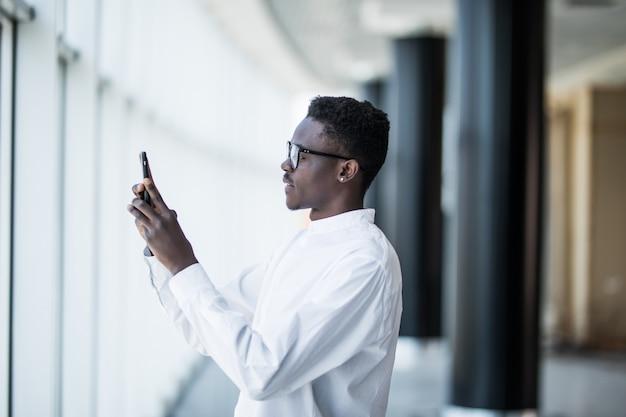 Afro-amerykański mężczyzna rozmawia selfie ze smartfonem robienia zdjęć w biurze