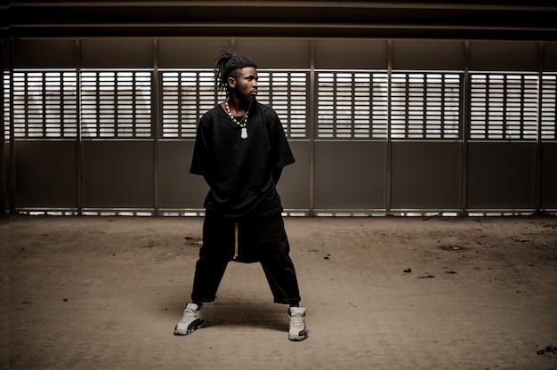Afro amerykański mężczyzna stojący z szeroko rozstawionymi nogami