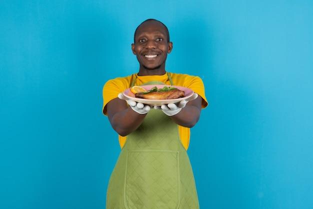 Afro amerykański mężczyzna w zielonym fartuchu oferujący talerz jedzenia na niebieskiej ścianie