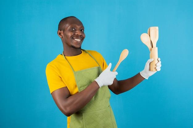 Afro amerykański mężczyzna w zielonym fartuchu trzyma drewniane narzędzia kuchenne na niebieskiej ścianie