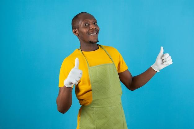 Afro amerykański mężczyzna w zielonym fartuchu trzyma kciuki na niebieskiej ścianie