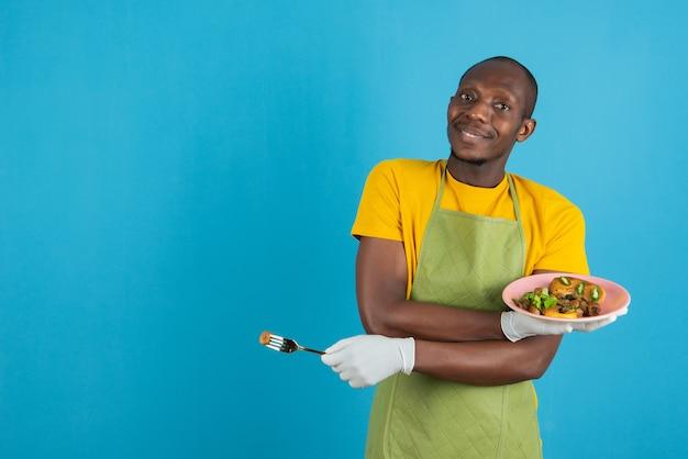 Afro amerykański mężczyzna w zielonym fartuchu trzyma talerz z jedzeniem na niebieskiej ścianie