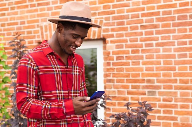 Afro amerykański mężczyzna za pomocą swojego telefonu komórkowego