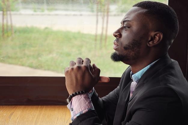 Afro amerykański zamyślony zmęczony młody biznesmen siedzi w kawiarni. portret młodego czarnego mężczyzny patrzy w okno odwraca głowę i patrzy na kamerę. brodaty młody facet nosi koszulę i marynarkę.