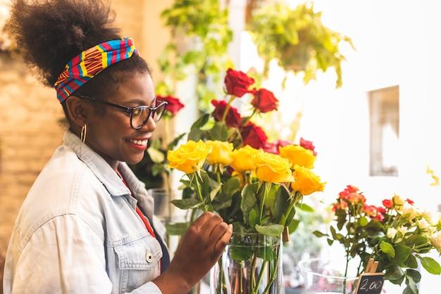 Afro amerykańskie nastoletnie dziewczyny pachnące żółte kwiaty róży.