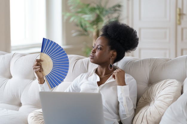 Afro biznes kobieta cierpiąca na udar cieplny siedzi w salonie w domu za pomocą machającego wentylatora