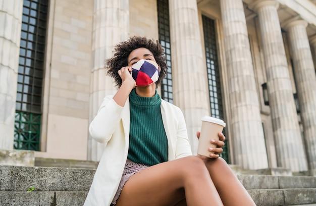 Afro biznes kobieta nosi maskę ochronną i rozmawia przez telefon, siedząc na schodach na zewnątrz na ulicy. koncepcja biznesowa i miejska.