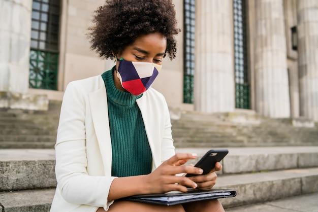 Afro biznes kobieta nosi maskę ochronną i używa swojego telefonu komórkowego, siedząc na schodach na zewnątrz na ulicy