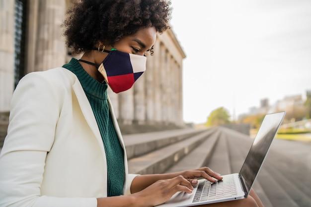 Afro biznes kobieta ubrana w maskę ochronną i za pomocą swojego laptopa siedząc na schodach na zewnątrz