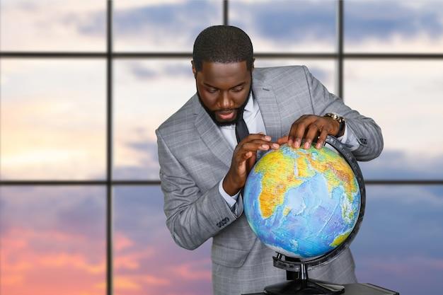 Afro biznesmen dotykając świata.