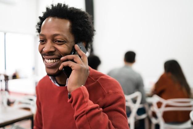 Afro biznesmen rozmawia przez telefon i pracuje w swoim miejscu pracy. pomysł na biznes.
