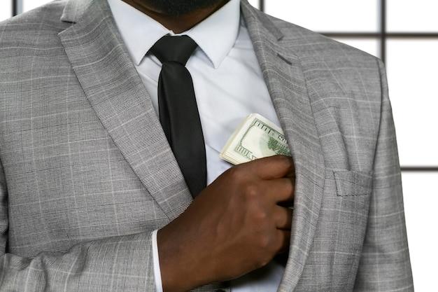 Afro biznesmen ukrywa pieniądze. bogacz na białym tle. nakarm chciwość. mistrz oszustwa.