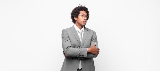 Afro biznesmen wątpi lub myśli, przygryza wargę i czuje się niepewnie i zdenerwowany, chcąc skopiować przestrzeń z boku