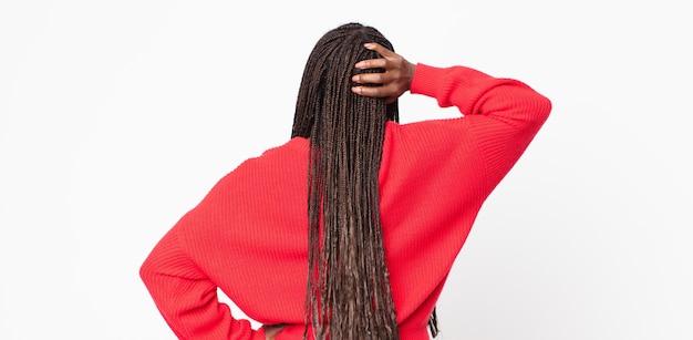 Afro czarna dorosła kobieta czuje się niezorientowana i zdezorientowana, myśląc o rozwiązaniu, z ręką na biodrze i innymi na głowie, widok z tyłu