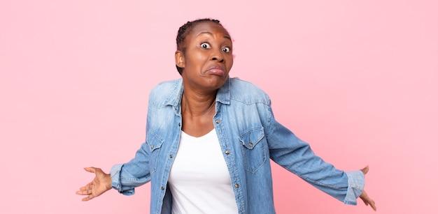 Afro czarna dorosła kobieta czuje się niezorientowana i zdezorientowana, nie mając pojęcia, całkowicie zaintrygowana głupim lub głupim spojrzeniem