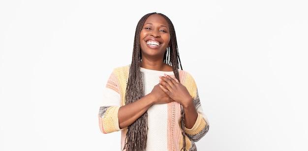 Afro czarna dorosła kobieta czuje się romantycznie, szczęśliwa i zakochana, uśmiechając się radośnie i trzymając się za ręce blisko serca