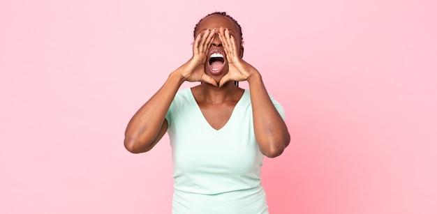 Afro czarna dorosła kobieta czuje się szczęśliwa, podekscytowana i pozytywna, wydając wielki okrzyk z rękami przy ustach, wołając