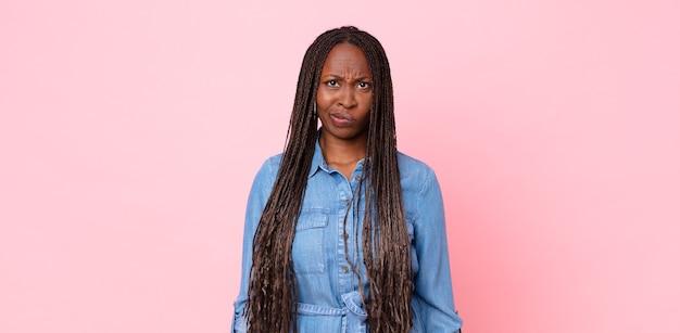 Afro czarna dorosła kobieta czuje się zdezorientowana i pełna wątpliwości, zastanawia się lub próbuje wybrać lub podjąć decyzję