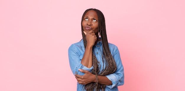 Afro czarna dorosła kobieta myśli, czuje się zwątpienie i zdezorientowana, z różnymi opcjami, zastanawiając się, którą decyzję podjąć