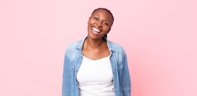 Afro czarna dorosła kobieta o dużym, przyjaznym, beztroskim uśmiechu, wyglądająca pozytywnie, zrelaksowana i szczęśliwa, relaksująca
