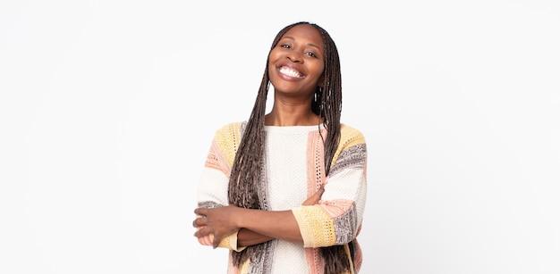 Afro czarna dorosła kobieta śmiejąca się radośnie ze skrzyżowanymi rękami, o zrelaksowanej, pozytywnej i zadowolonej pozie