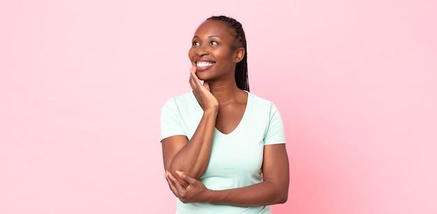 Afro czarna dorosła kobieta uśmiecha się radośnie i marzy lub wątpi, patrząc w bok